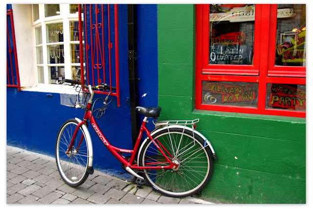 bicycle propped on a very colourful wall