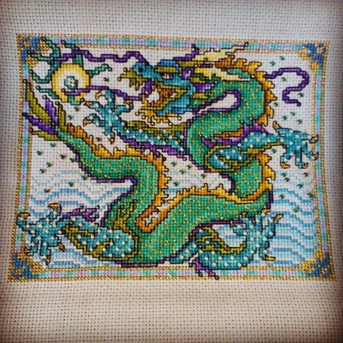 A cross stitched sea dragon in green, blue, and purple