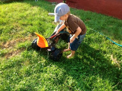 grandson playing with garden hose on the lawn