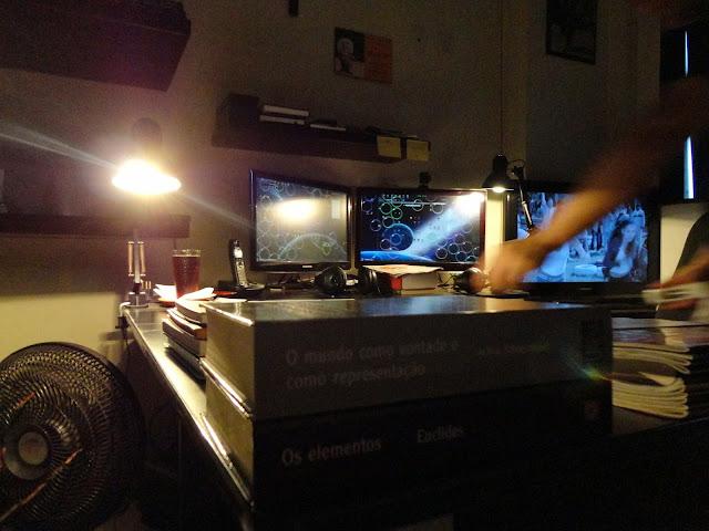 Seu ambiente de trabalho entre livros e computadores.