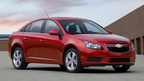 Front 3/4 view of red 2011 Chevrolet Cruze parked on rooftop garage