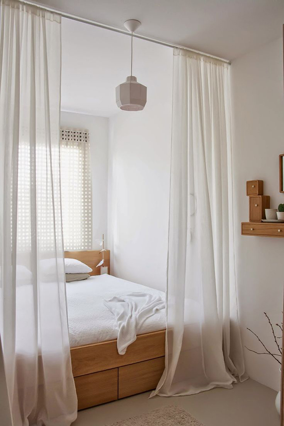 Cozy bed behind sheer curtains | Holly Marder via Decor8