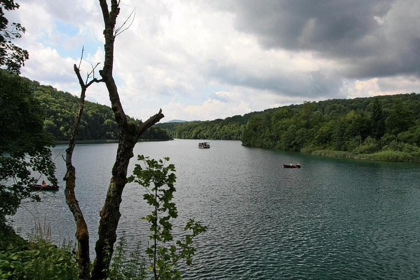 Paisagem do lago com um trono em primeiro plano e algumas plantas, dois barcos a navegar, a vegetação ao fundo e o céu nublado