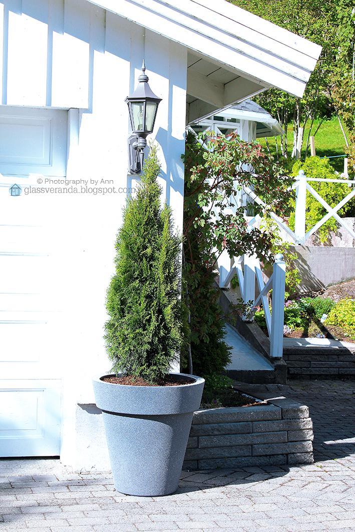 Glassveranda: ekstra store blomsterkrukker pynter opp foran garasjen