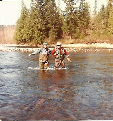 Two fly fishers wading across a river arm in arm.