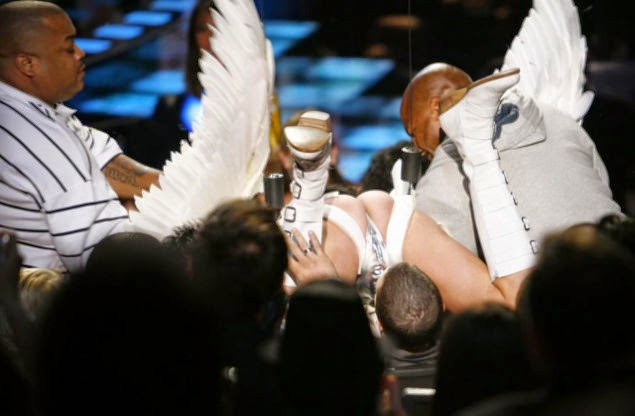 Sacha Baron Cohen, wearing a jockstrap and wings, lands on Eminem's head at an MTV award show.