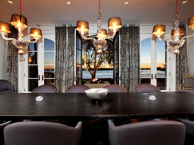 dining room with view of the sunset over the ocean, three crystal chandelier light fixtures, a long dark table with leather seats