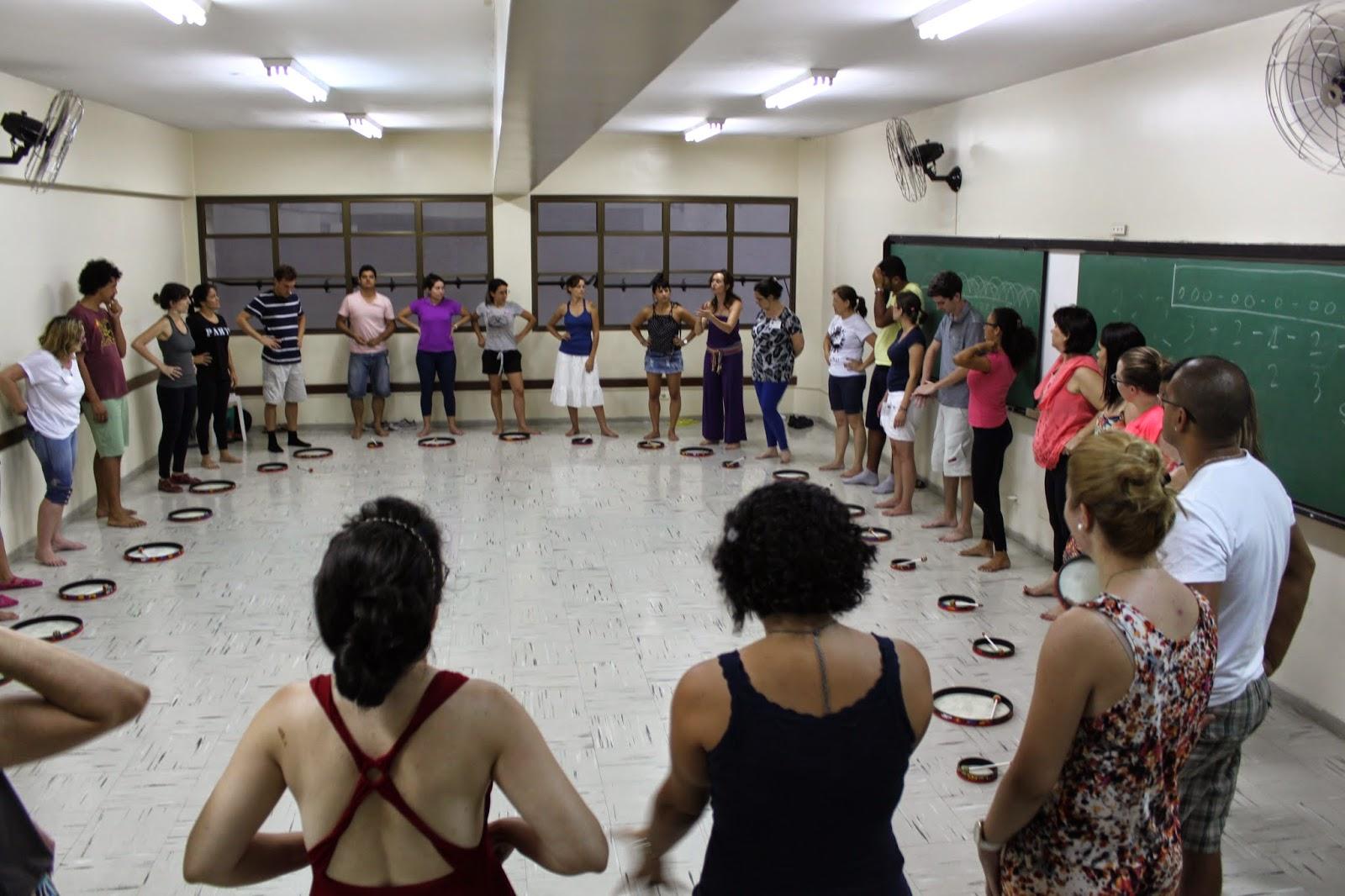 Descrição da Foto: Um grupo de aproximadamente 30 pessoas, estão todos de pé. No chão, à frente de cada participante um tambor.