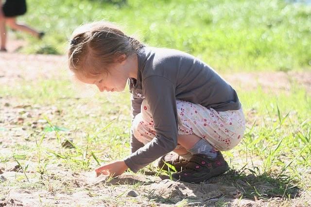 Kind betrachtet etwas am Boden