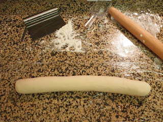 a rolling pin and a scraper are on top of a thick dough rough