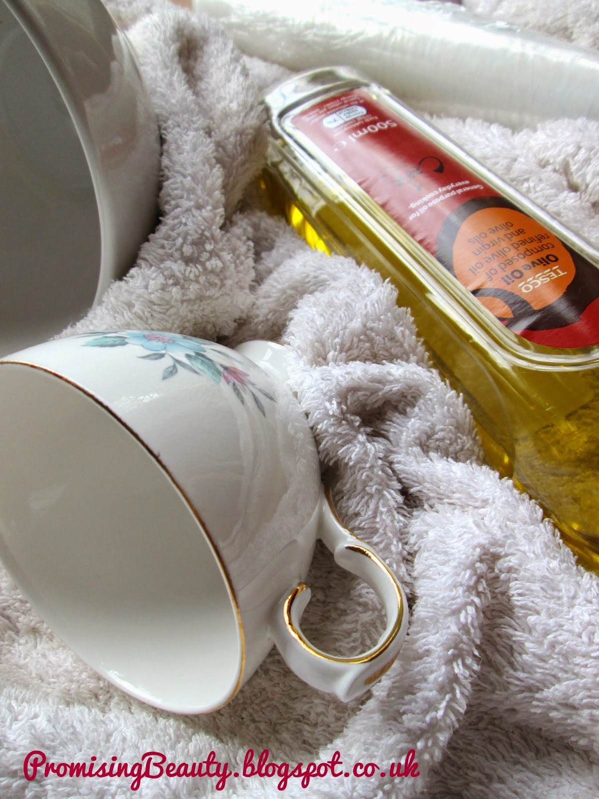 DIY oil treatment for your hair. Olive oil, cling film or seran wrap and fluffy white towels. Bone China teacup with gold edging.