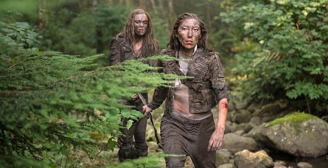 Na imagem: Cena de The 100 com duas mulheres no meio da mata muito sujas de lama e descabeladas andando com cara de sofrimento