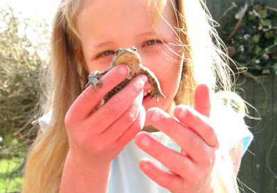 girl with frog countryside children mucky fun