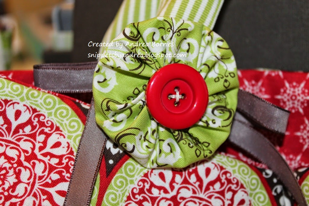 Photo showing a close-up view of one of the fabric yoyos made with green fabric, a red button in the center and brown ribbon.