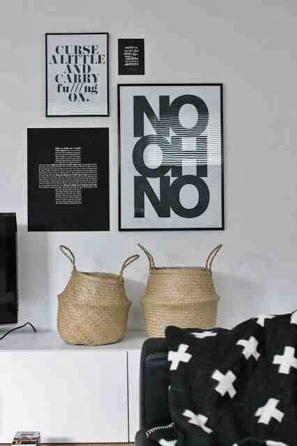 Design skandynawski, skandynawskie dekoracje, grafiki w czarnych ramach, czarny koc z białym krzyżykiem