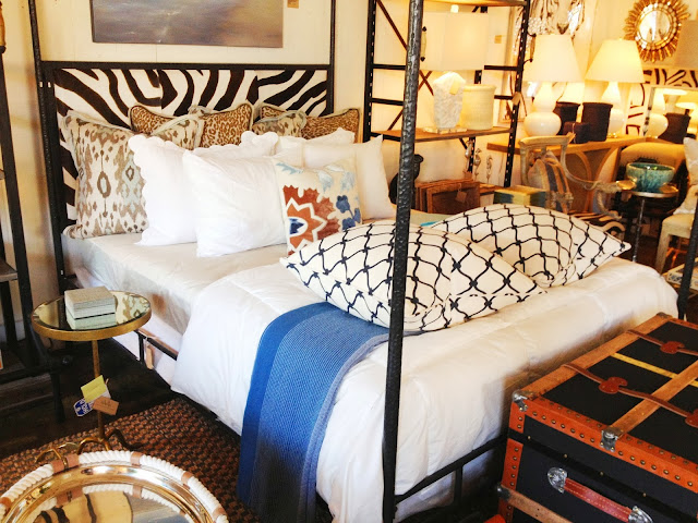 COCOCOZY Fence pillows in Navy on an iron canopy bed with a zebra print headboard at Mecox Gardens in Los Angeles, CA