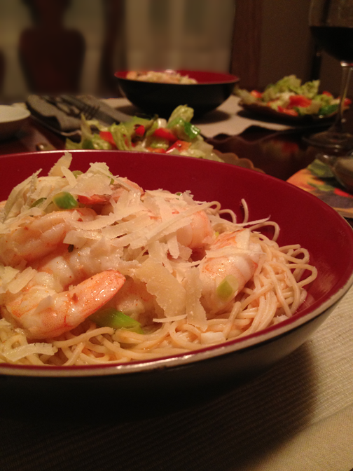 Close up of shrimp scampi on a bed of pasta with cheese.