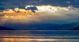 Scenic Crepuscular rays of light poke through the clouds on the Mountains of Okanagan Valley viewed from Kelowna by Chris Gardiner Photography www.cgardiner.ca