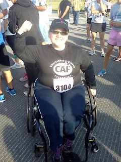 "Author wearing a baseball cap saying ""Iron Girl,"" black long-sleeved shirt with ""Challenged Athletes Foundation,"" racing number 3104, blue workout pants, sitting in blue-framed wheelchair, flexing one arm.  Pic taken before my first wheeled 5k race"