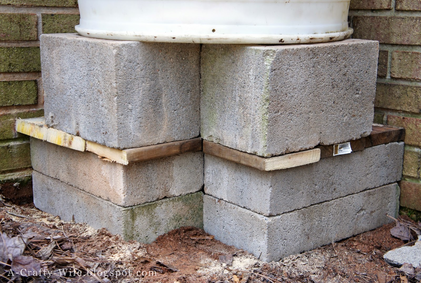 Elevate rain barrel off ground with cinder blocks | A Crafty Wife