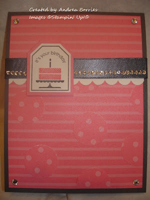 Gray card with pink striped paper as the background. Gray ribbon, white scalloped card stock and rhinestones go across the card. Focal image is a tag with a pink birthday cake.