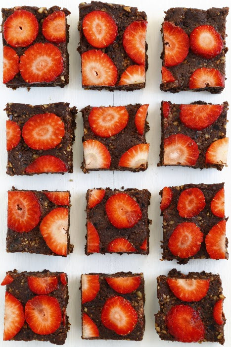 Squares of raw brownies with strawberries on a white background