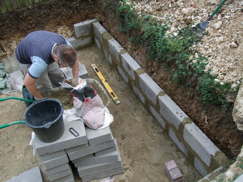 Alternative eden exotic garden and the walls go up for Concrete block pond construction