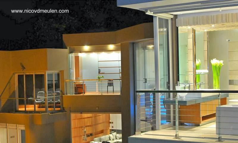Planta superior vidriada de la residencia  vista desde afuera en la noche