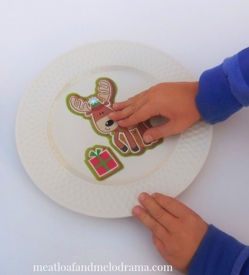 boy putting reindeer window cling on plate