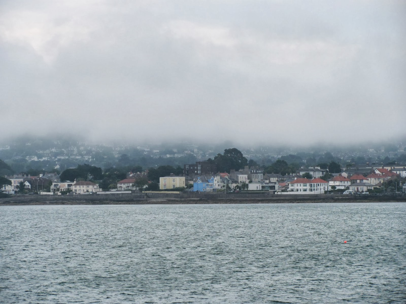 Fog rolls down from the hill over the village at Dun Laoghaire, Co. Dublin, Ireland