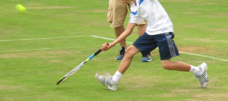 イギリス コッツウォルズ チェトナムのテニスクラブ 芝のコートでプレイするジュニアテニス