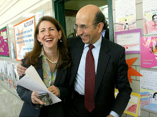 Joel Klein hugging a teacher and smiling