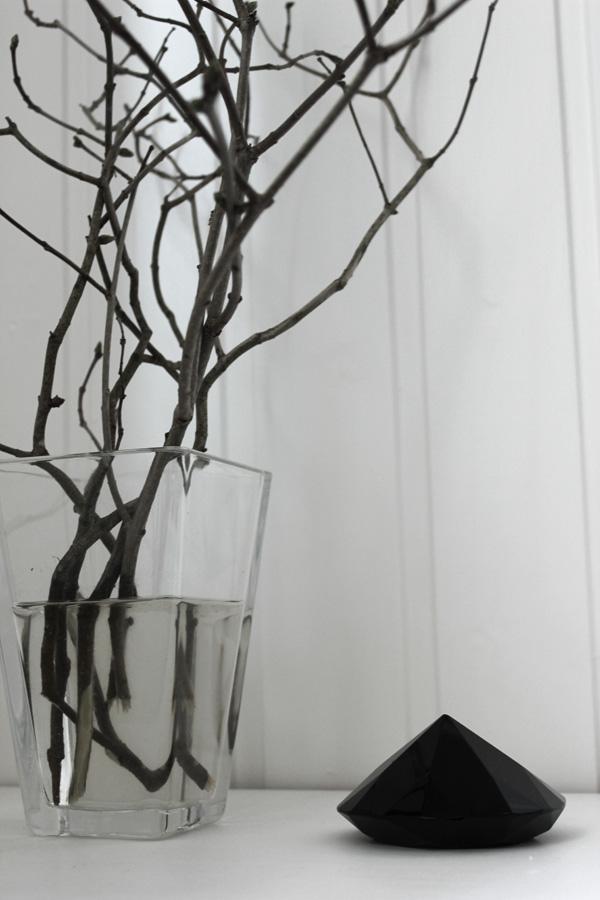 Kvistar från syrenbuske i vas. Naturmaterial i inredningen. Svart diamant av glas som inredningsdetalj.
