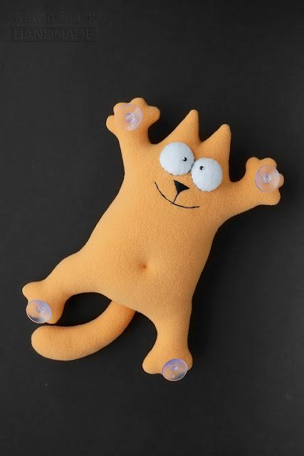 Кот Саймона - игрушка на присосках в машину. Персикового цвета.