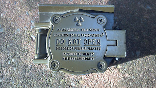 back of a lensatic compass that say do not open because it contains radioactive material