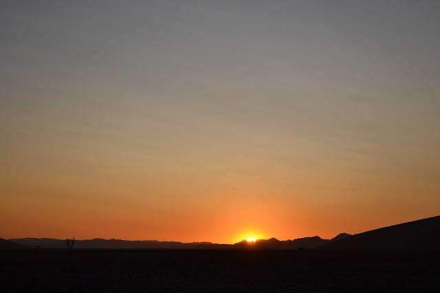 Sun peeking over mountains in Sossusvlei