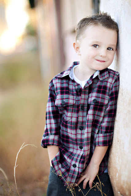Child poses against a wall with his eyes filled with the mischievous ideas in his head