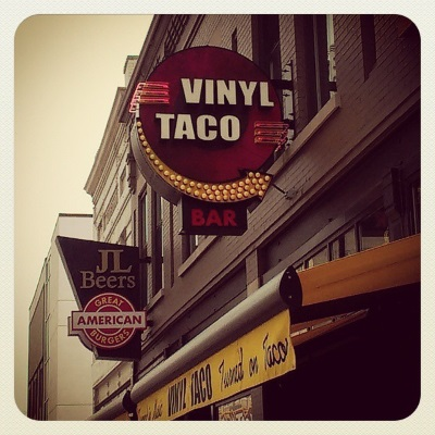 A circular sign is attached perpendicular to a brick building. It reads 'Vinyl Taco Bar' and features a gold arrow pointing at the building.