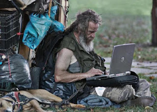 Homeless guy logging on to laptop computer Dell Hobo park wifi internet checking email