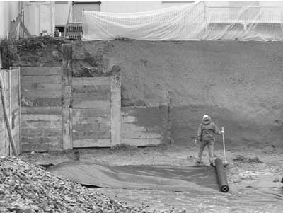 Where slope support turns the corner in this excavation and the soil can be sloped at a lesser angle, less expensive shotcrete takes the place of soldier beams and lagging.
