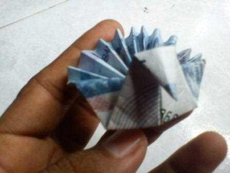 Seni origami melipat uang kertas bentuk burung merak