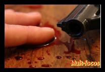 Uma mão sangrando ao lado de um revolver