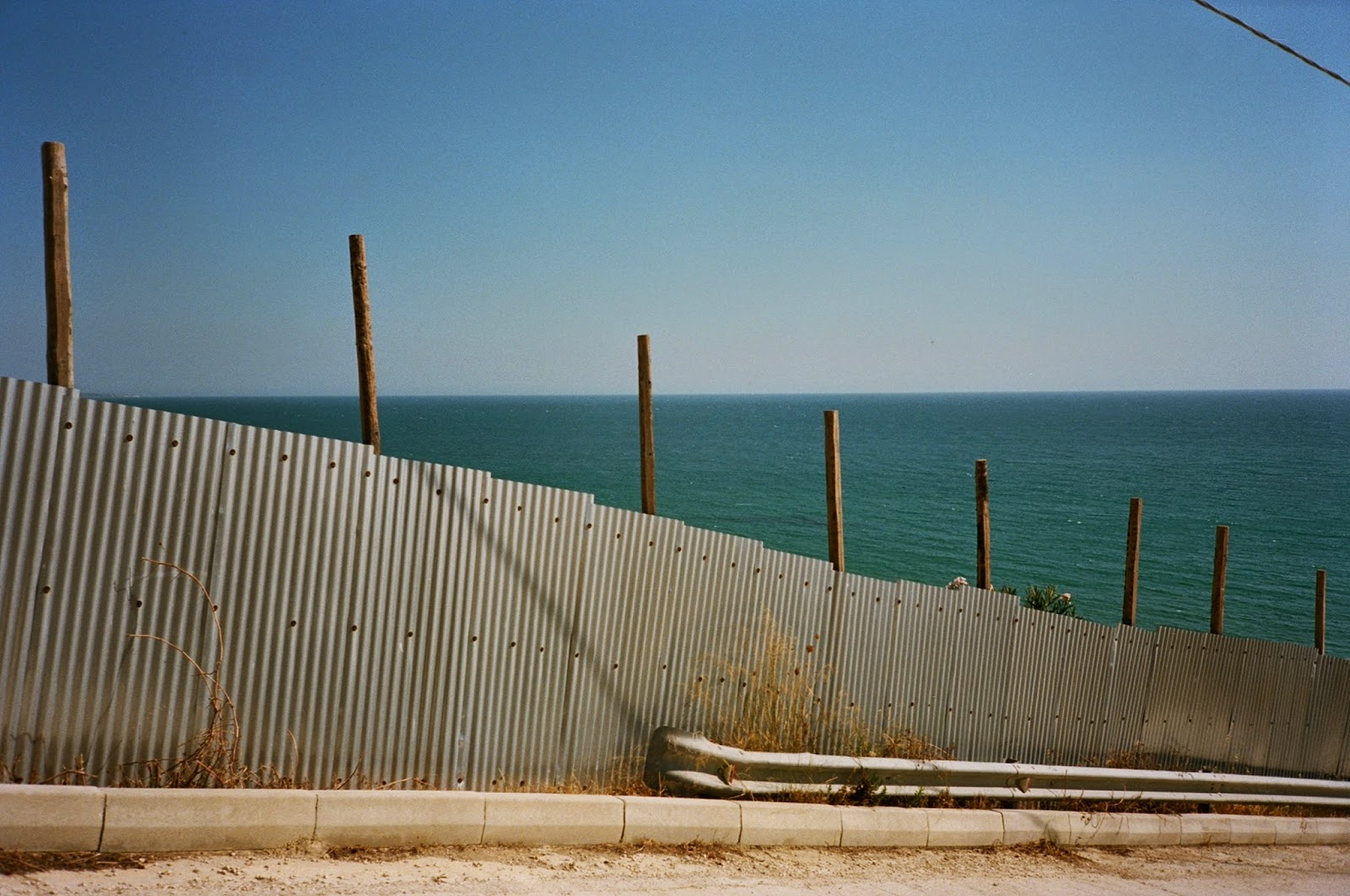 CORRUGATED SHEET METAL, BARACADE, DEVELOPMENT SITE, COASTAL VIEW IN SOUTHERN SICILY, AGRIGENTO, SCIACCA, SICILY © VAC 100 DAYS 4 MILLION CONVERSATIONS