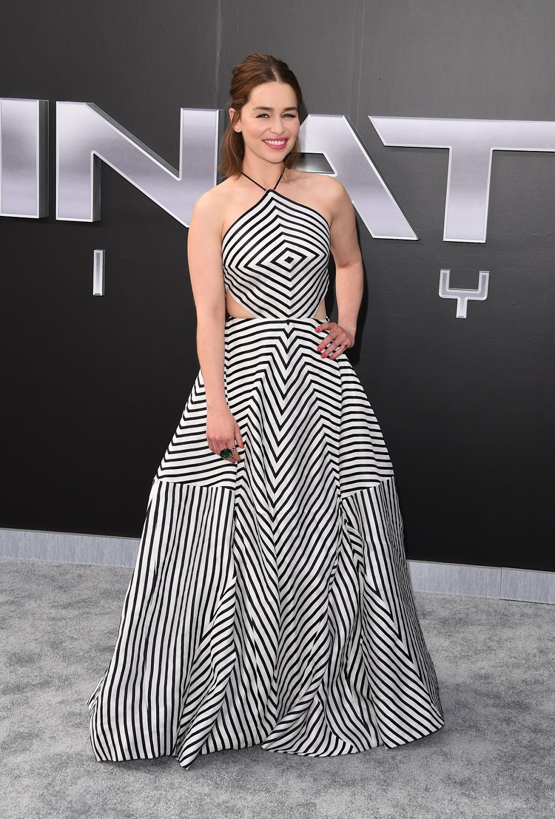 Emilia Clarke shows skin in a striped dress at the 'Terminator Genisys' Hollywood premiere