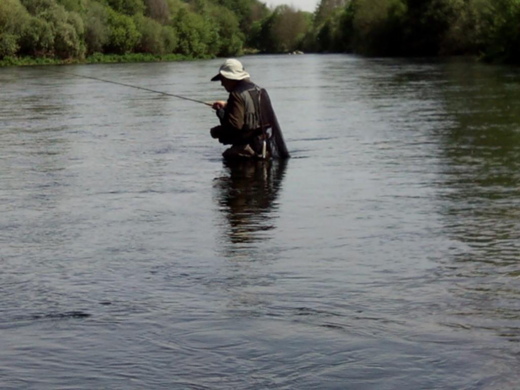pescador en el cauce del rio manejando la caña