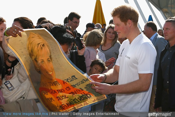 Prince Harry looks at a photo of his mother, Princess Diana shown by Faasiu Gaee from Samoa as he meets members of the public at an event to promote the 2015 FIFA U-20 World Cup which will be hosted by New Zealand