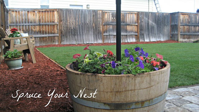 yard umbrella, wine barrel, petunias
