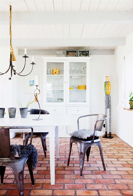 Metal cafe chairs with furry modern cushions surround a traditional white farmhouse table in the home's dining area which also as a chandelier and white glass door cabinet