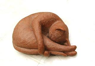 Style figuratif : chat dormant en boule, pattes arrière étirées