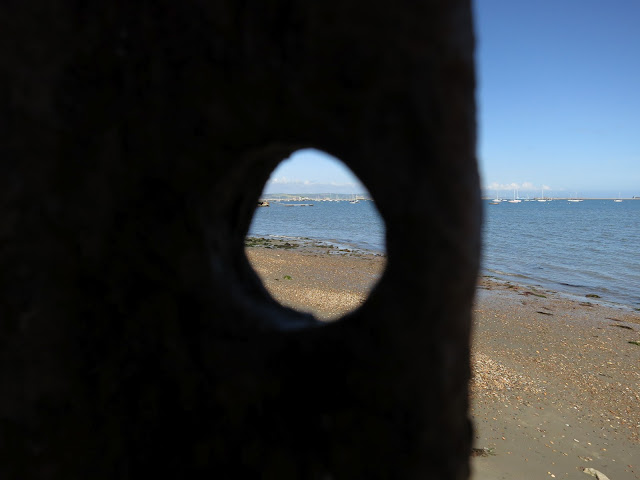 Sea and beach seen both through a metal hole and not.